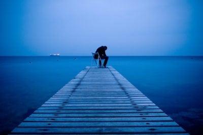 Man sitting alone on a pier