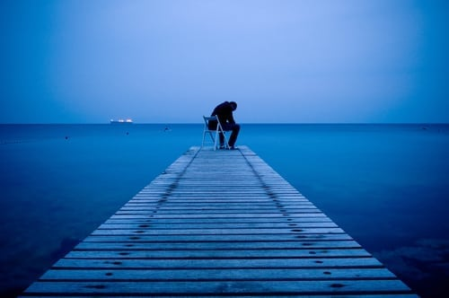 Man sitting alone on a pier